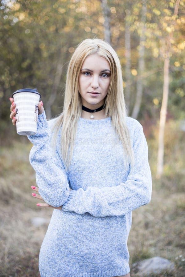 Trinkender Kaffee der Herbstfrau Fallkonzept der jungen Frau heißes Getränk von der Wegwerfkaffeetasse genießend lizenzfreie stockfotografie