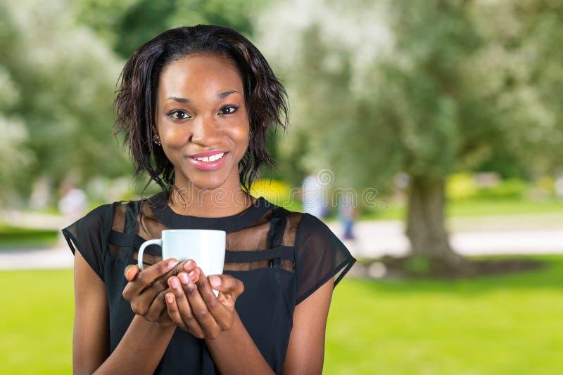 Trinkender Kaffee der jungen afrikanischen Geschäftsfrau stockfotos
