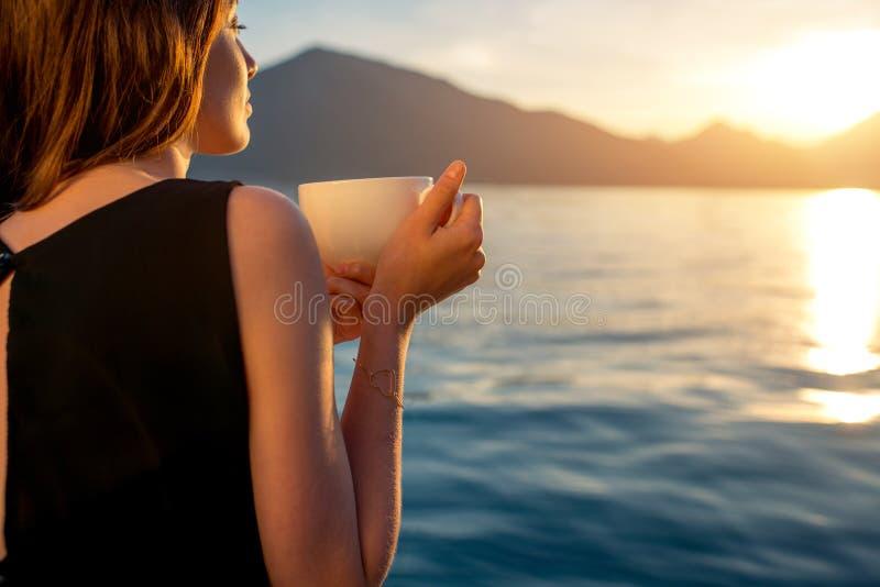Trinkender Kaffee der jungen Frau auf dem Pier bei Sonnenaufgang stockbilder