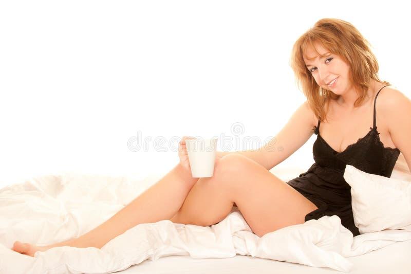 Trinkender Kaffee der jungen Frau im Bett stockbilder