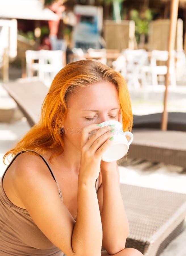 Trinkender Kaffee der jungen Frau am Strand lizenzfreie stockfotos
