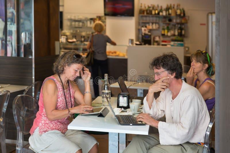 Trinkender Kaffee der Leute und Arbeiten an Laptop lizenzfreie stockfotos