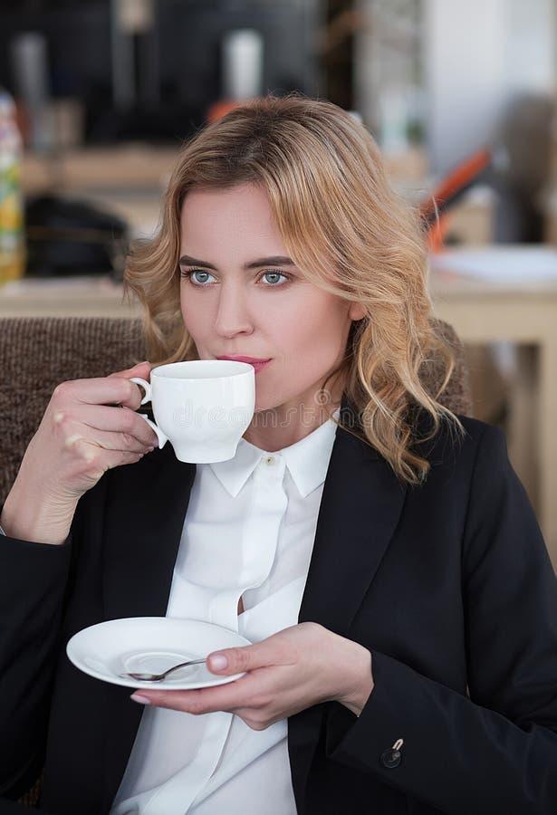Trinkender Kaffee der schönen Geschäftsfrau im Büro lizenzfreie stockfotos