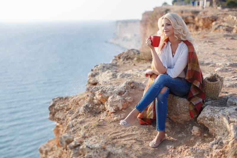 Trinkender Kaffee der Schönheit, der auf dem felsigen Ufer sitzt lizenzfreies stockfoto