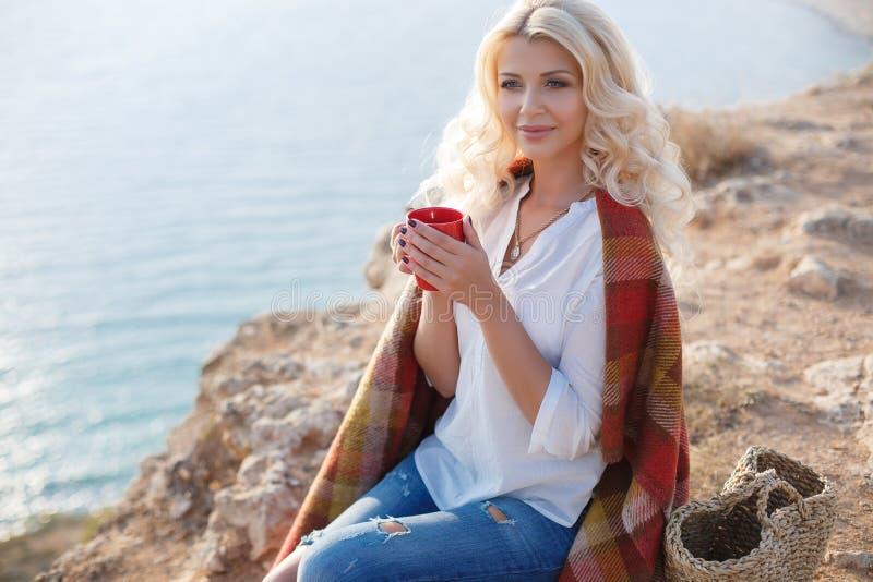 Trinkender Kaffee der Schönheit, der auf dem felsigen Ufer sitzt lizenzfreie stockfotografie
