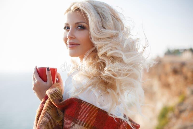 Trinkender Kaffee der Schönheit, der auf dem felsigen Ufer sitzt lizenzfreie stockfotos
