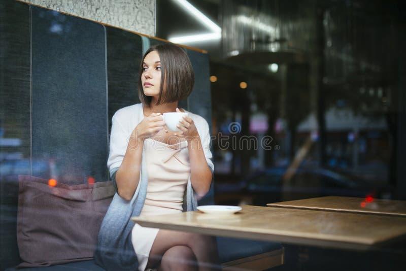 Trinkender Kaffee der Schönheit im Stadtcafé lizenzfreie stockbilder
