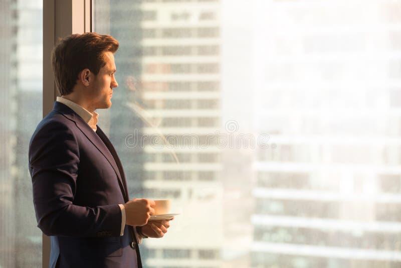 Trinkender Kaffee des ernsten nachdenklichen Geschäftsmannes, Sonnenaufgang betrachtend lizenzfreie stockfotografie