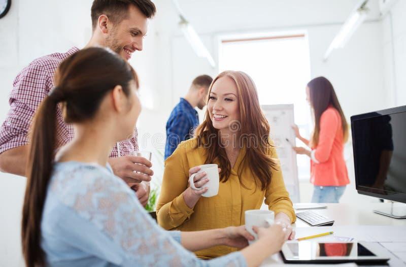 Trinkender Kaffee des glücklichen kreativen Teams im Büro lizenzfreie stockfotos