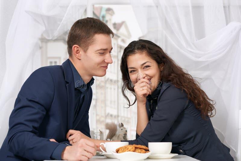 Trinkender Kaffee des glücklichen Paars und Habenspaß nahe Fenster mit einer Straßenansicht - reisen Sie und lieben Sie Konzept lizenzfreie stockbilder