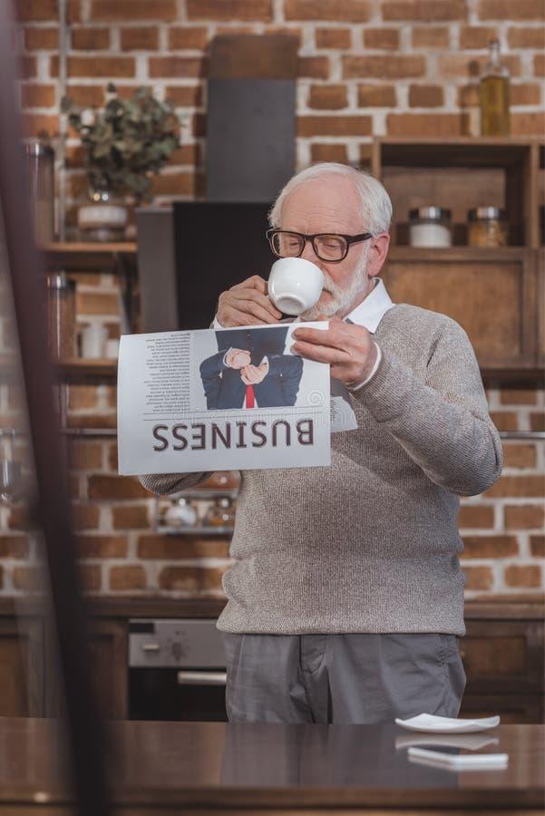 trinkender Kaffee des hübschen grauen Haarmannes und Ablesen der Wirtschaftszeitung stockfotografie
