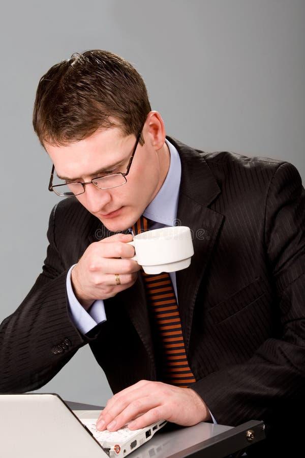 Trinkender Kaffee des jungen Geschäftsmannes am Arbeitsplatz stockfoto