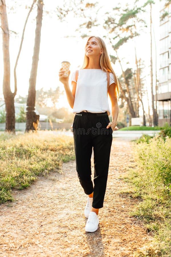Trinkender Kaffee des jungen schönen Mädchens, der um die Stadt, herein geht lizenzfreie stockbilder