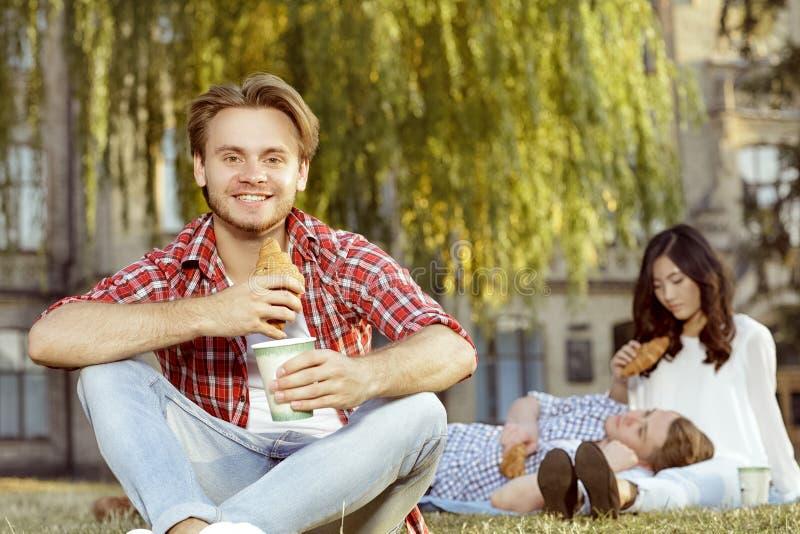 Trinkender Kaffee des Kerls und in einem Park stockfoto