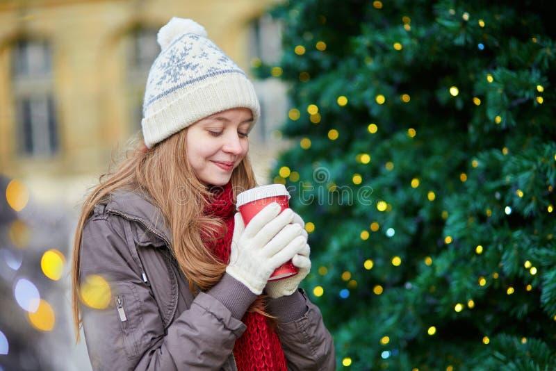 Trinkender Kaffee des Mädchens nahe verzierte Weihnachtsbaum lizenzfreie stockbilder