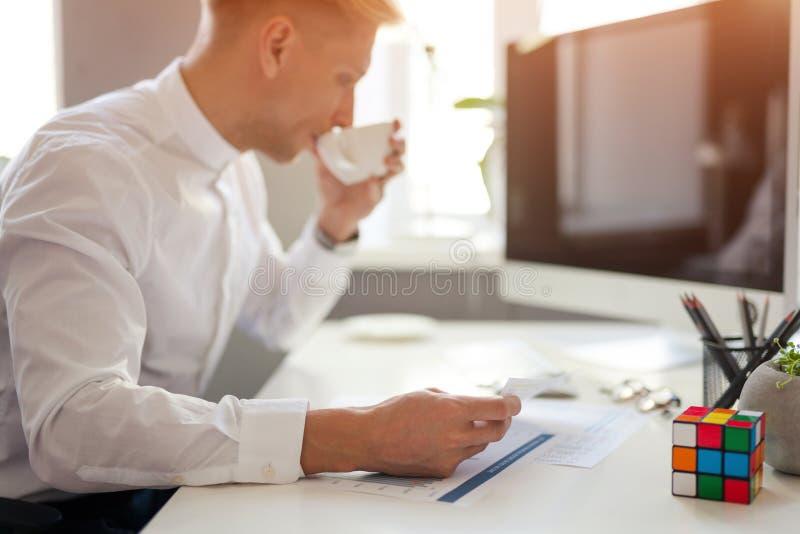 Trinkender Kaffee des Mannes am Arbeitsplatz lizenzfreies stockfoto