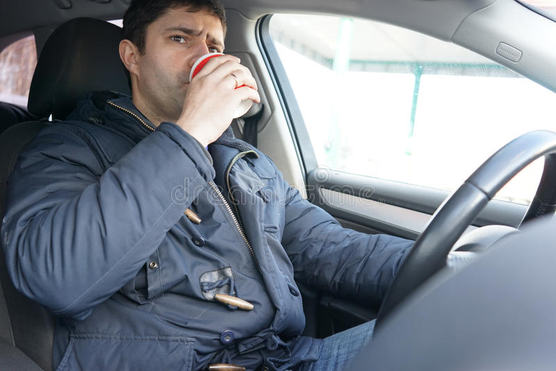 Trinkender Kaffee des Mannes im Auto stockfotografie