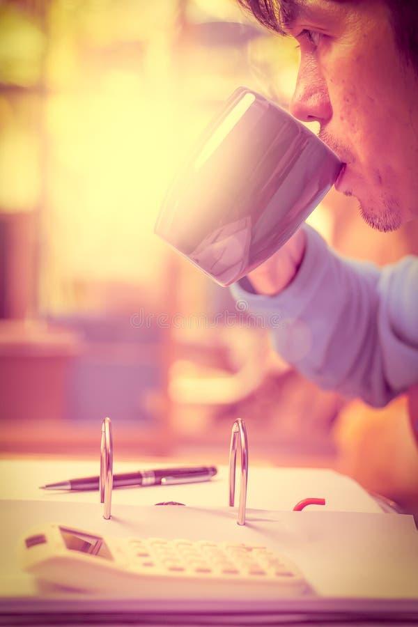 Trinkender Kaffee des Mannes und Belegdatei lizenzfreie stockfotos