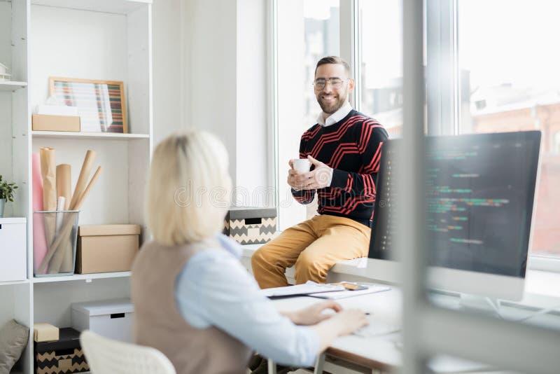 Trinkender Kaffee des netten Büromannes bei der Unterhaltung mit Kodierer stockbild