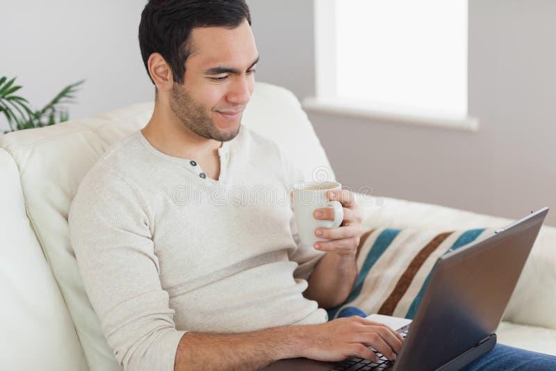 Trinkender Kaffee des ruhigen attraktiven Mannes beim Arbeiten an seinem Laptop lizenzfreie stockbilder