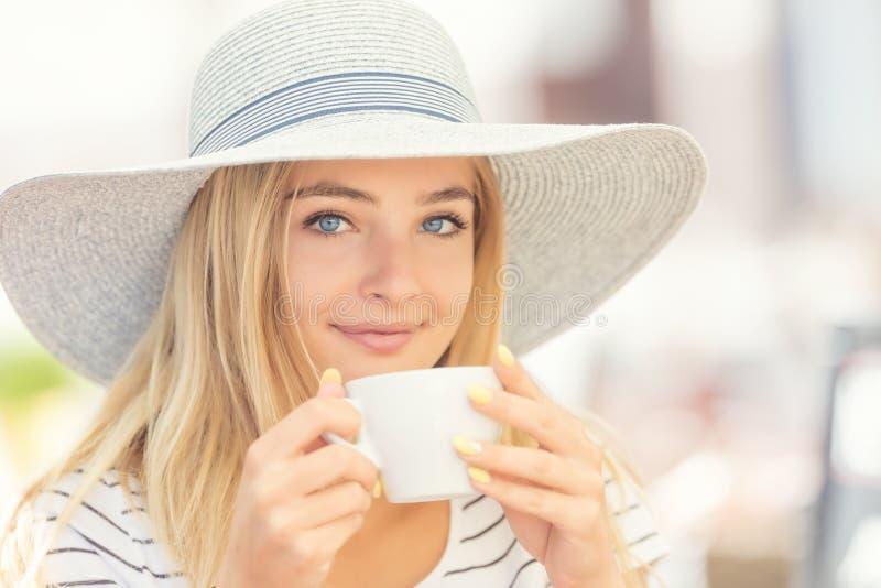 Trinkender Kaffee des schönen Mädchens in einer Caféterrasse Junge Frau des Sommerporträts lizenzfreie stockbilder