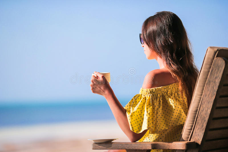 Trinkender Kaffeecappuccino der jungen Frau, der Strandansicht genießt lizenzfreie stockfotografie