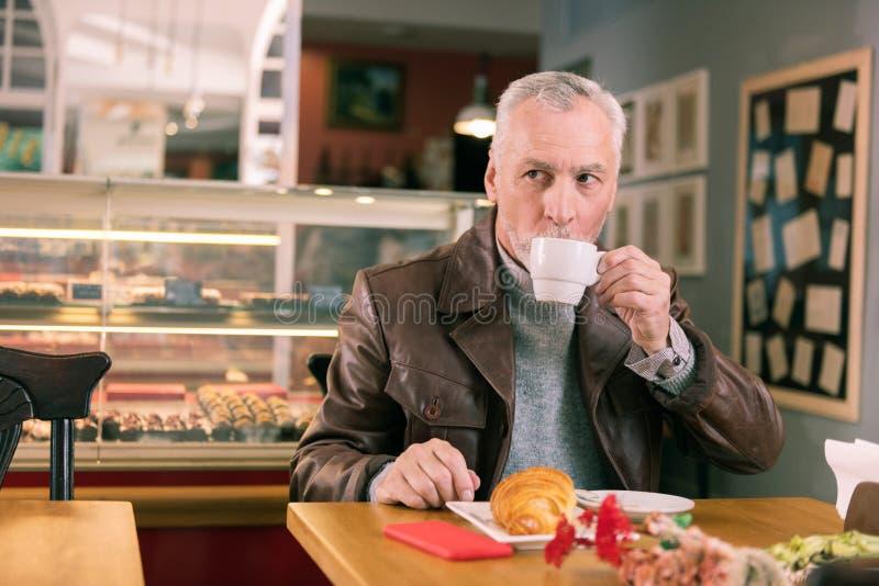 Trinkender Morgenkaffee des dunkeläugigen reifen Mannes in der französischen Bäckerei lizenzfreie stockfotos