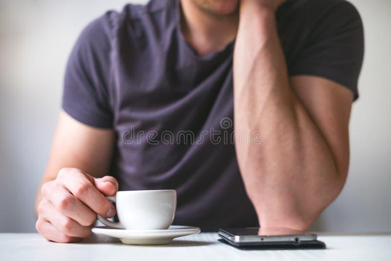 Trinkender Morgenkaffee des jungen Mannes und halten Handy Süßes Hörnchen und ein Tasse Kaffee im Hintergrund Bemannen Sie das Ha stockbild