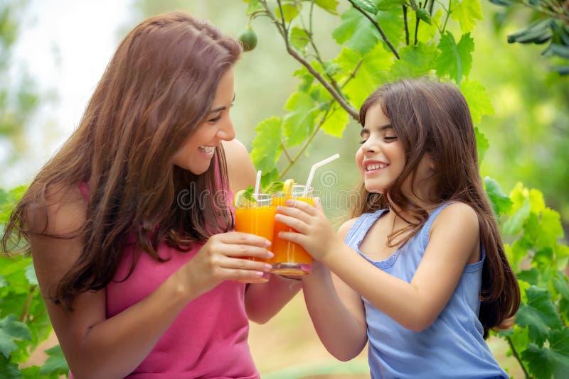trinkender Saft der gl?cklichen Familie lizenzfreies stockfoto