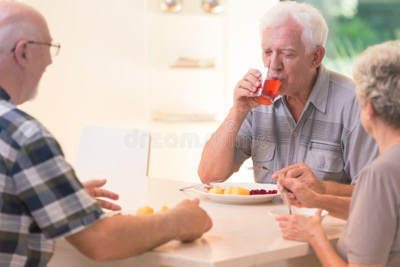 Trinkender Saft des älteren Mannes lizenzfreie stockbilder