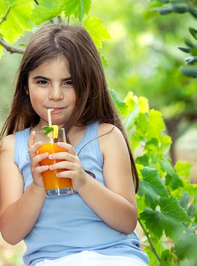Trinkender Saft des gl?cklichen M?dchens stockfoto
