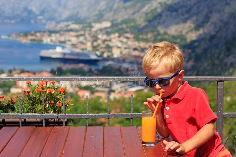 Trinkender Saft des kleinen Jungen im Café lizenzfreies stockbild