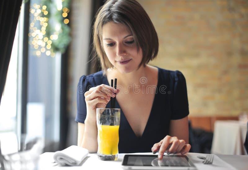 Trinkender Saft des Mädchens und Betrachten der Tablette lizenzfreies stockfoto