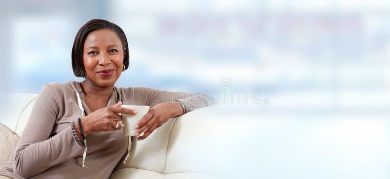 Trinkender Tee der afro-amerikanischen Frau lizenzfreie stockbilder
