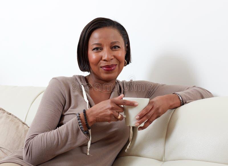 Trinkender Tee der afro-amerikanischen Frau stockfotos