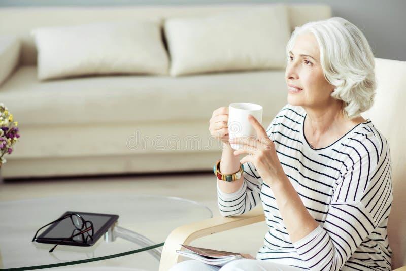 Trinkender Tee der angenehmen Greisin lizenzfreie stockfotos