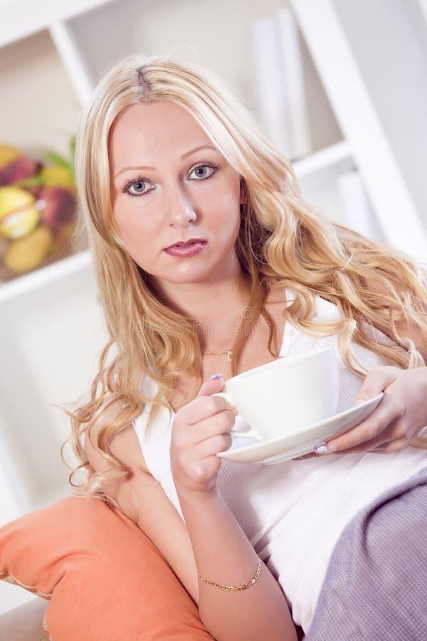 Trinkender Tee der Frau auf Couch stockbilder