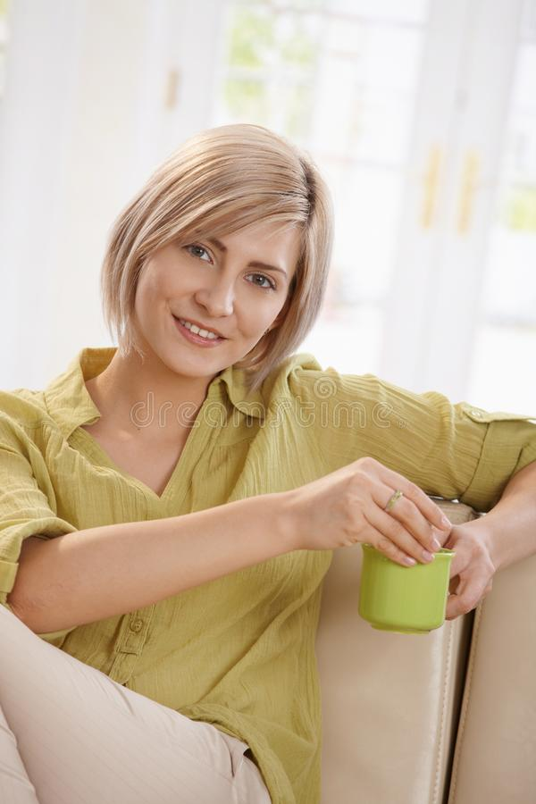 Trinkender Tee der Frau auf Couch zu Hause lizenzfreie stockfotos