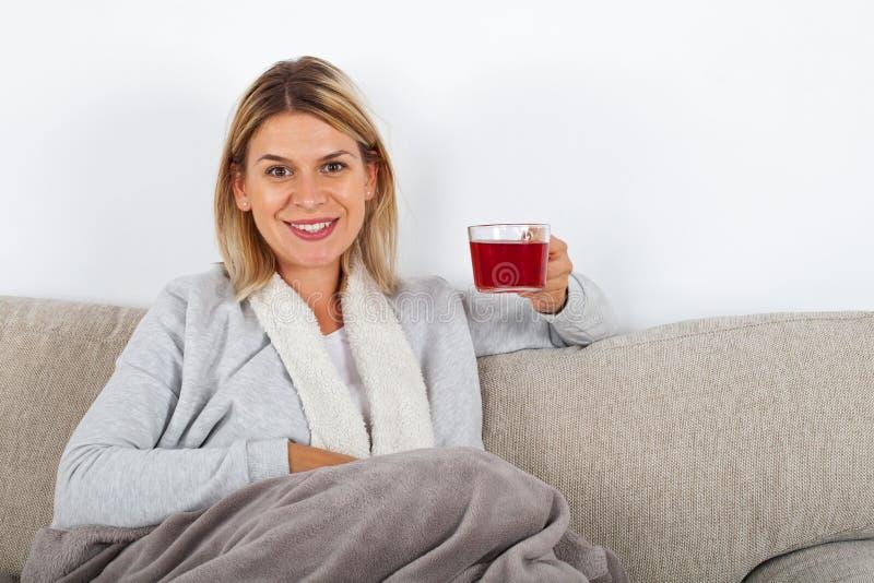 Trinkender Tee der Frau auf dem Sofa stockbilder