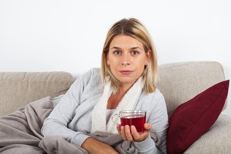 Trinkender Tee der Frau auf dem Sofa stockfoto