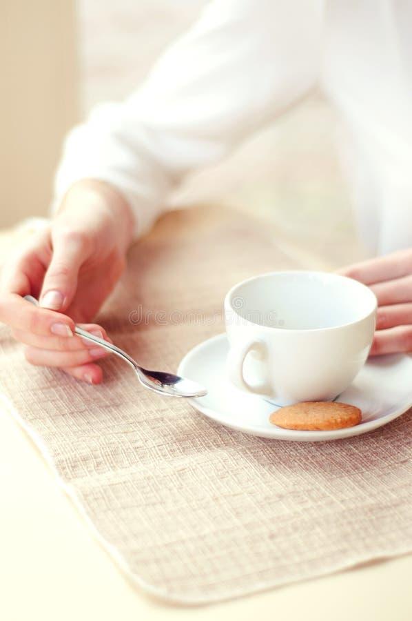 Trinkender Tee der Frau in einem Café übergibt Nahaufnahme lizenzfreies stockbild