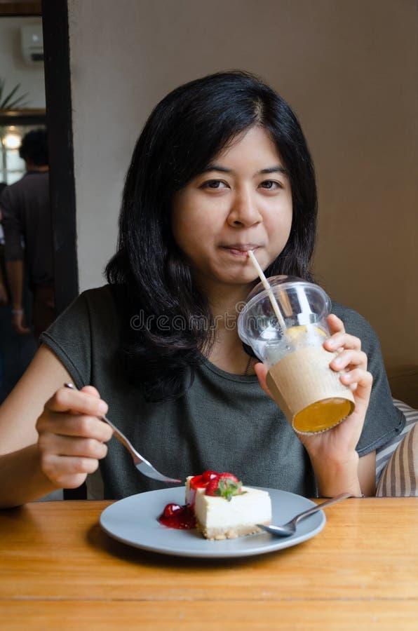 Trinkender Tee der Frau mit Erdbeerkäsekuchen stockbilder