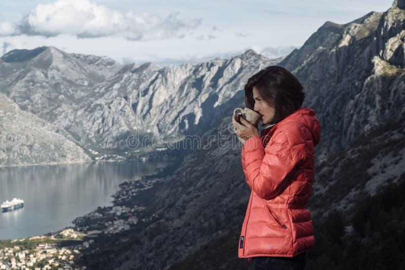Trinkender Tee der glücklichen Wandererfrau in der Naturfallberglandschaft lizenzfreie stockbilder