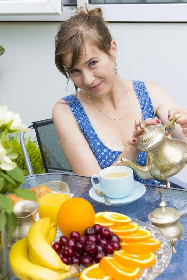 Trinkender Tee der jungen Frau draußen lizenzfreie stockbilder