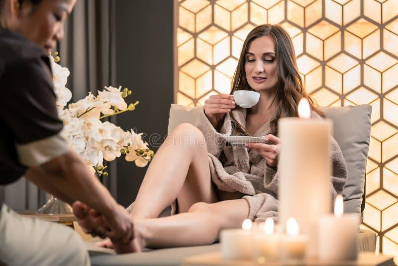 Trinkender Tee der jungen Frau während traditionellen Balinesefuß massag stockbild