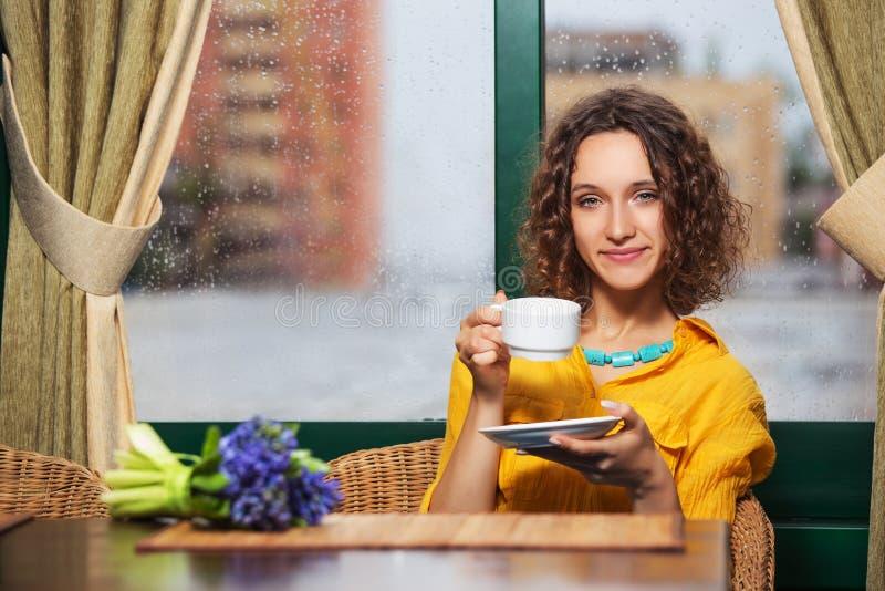Trinkender Tee der jungen Modefrau am Restaurant stockfotografie