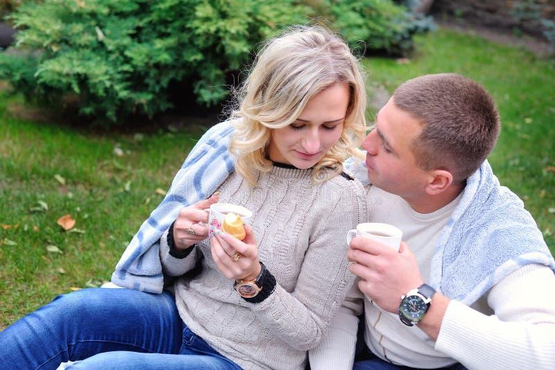 Trinkender Tee der jungen Paare im Park stockfoto