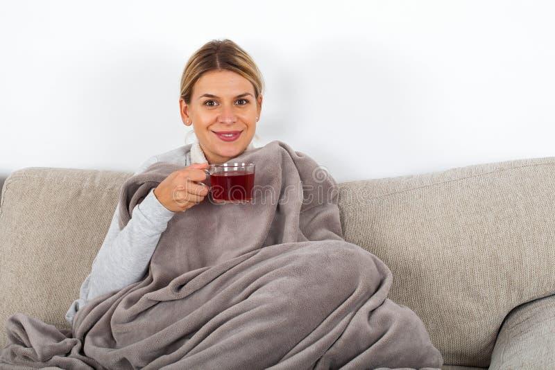 Trinkender Tee der kranken Frau lizenzfreie stockfotografie