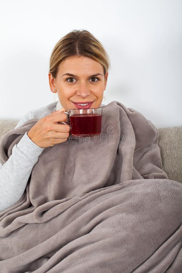 Trinkender Tee der kranken Frau lizenzfreie stockbilder