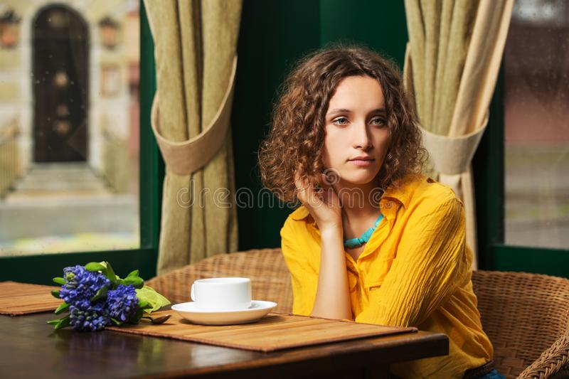 Trinkender Tee der traurigen jungen Modefrau am Restaurant stockbild